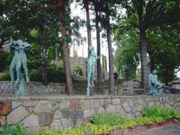 бронзовые скульптуры под кипарисами и туями