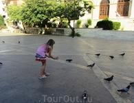 На площади Св. Екатерины очень много голубей. Их подкармливают и отдыхающие и сами греки. Ну а девочка их ловит.