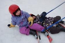 Инструктор обучает детей катанию на лыжах