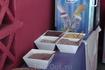 Четыре сорта мюсли, на переднем плане - какао, за ними - холодильник с йогуртами.