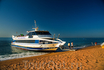 Катер подходит на пляж, чтобы взять пассажиров до Бланеса