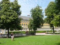 За деревьями выглядывает часть здания Боннского Университета.