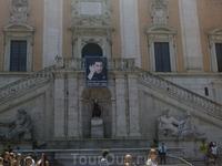 "Римский муниципалитет. На балконе портрет Гилада Шалита. Под ним в нише статуя ""Ликующий Рим"". Слева и справа от статуи символики Тибра и Нила."