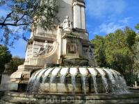 Фонтан, обратная сторона памятника Сервантесу, украшен гербами испаноязычных стран. Сверху - статуя Изабеллы Португальской, слева - стилизованная фигура ...