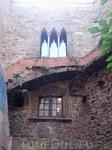 Это двор замка. Он довольно мал, и вокруг встают высокие стены замка...