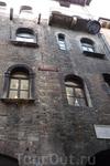 Верона. Арка  справа и  над ней доска  с  мраморным  изваянием герба семьи  Дель Капелло - шляпка .