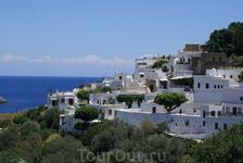 Белоснежные домики Линдоса  на фоне синего моря, выглядят райским оазисом