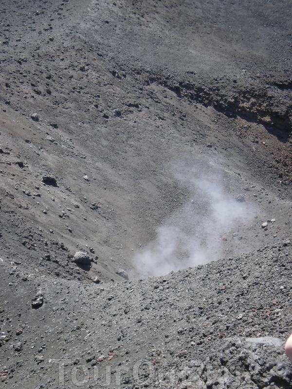 """Из открытого в земле """"живого"""" кратера поднимается пар."""