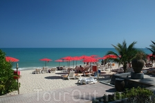 Пляж отеля Викендер. Приятное сочетание голубого моря и пляжных зонтиков алого цвета .