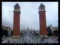 две великолепные башни, построенные по типу колокольни на площади Сан-Марко в Венеции, выступают между Палау Насиональ и Пласа де Эспанья. Внизу, монументальный фонтан, возвышающийся в центре площади.