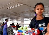 Девочка торгует на пароме через реку Янгон