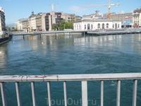 Знаменитый мост в месте истока реки Рона из Женевского озера. Правее - фонтан, левее - Кемпински, сзади - цветочные часы и женевский собор.