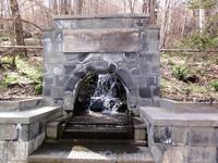Камень-посмящение на аллее источников в парке