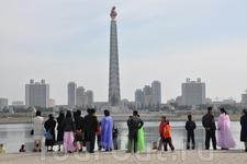 Трудящиеся рассматривают Памятник чучхе в столице.
