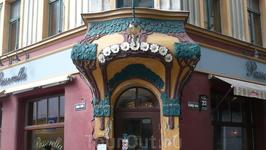 Угол здания, оформленный в виде кроны цветущего дерева. Над стилизованной кроной помещено изображение солнца. Здание было спроектировано в 1903 году, а ...