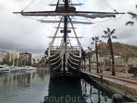 Древний корабль, грозное чье-то судно, тешит зевак и украшает пляж.