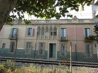 Дом на набережной, перед ним огороженная ветка железной дороги