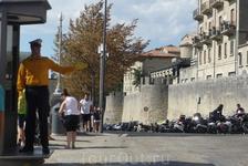 Полицейский движением левой руки указывает вход в крепость Сан-Марино.