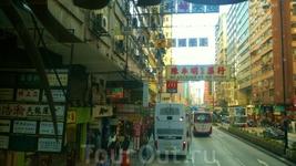 А вот и самое сердце одного из центральных районов Гонконга с неширокими улицами и высокими домами с большим количеством низко висящих вывесок, визуально ...
