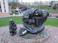 Памятник уличному музыканту,на удачу надо положить денежку в кошелёк,пуделю потереть лапку,а музыканту-нос.За скульптурой виден амфитеатр Славянский базар ...