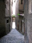 Улочки Сиены. Город окружен стеной с несколькими воротами, со средневековых времен он сохранил свой первоначальный облик суровой недоступности. Улицы вымощены ...