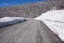 Единственное место, где мы в этот жаркий июль встретили высокие снежные бортики в горах. Впереди - каменная дамба на озере Styggevatnet. Это озеро – замечательное ...