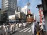 В момент продвижения колесниц мужчины в белых одеждах с опахалами по традиции стоят наверху и разбрасывают людям вокруг символические священные тимаки ...