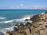 Волны разбиваются об острые камни, брызгаясь на туристов.