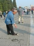 Утром пенсионеры собираются в парках.Танцую,поют,играют, На этой фотографии мужчина показывает искусство каллиграфии. Рисует водой на  дорожке