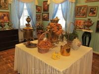 Стол в центре комнаты с самоваром, заварочными чайниками, сахарницами, пряниками, баранками и сушками.