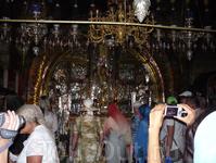 Голгофа – это небольшая скала или холм, где был распят Иисус Христос. Люди ведут съемку на фото и видеокамеры.