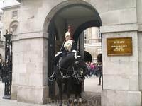 """Королевский гвардеец при полном параде. На табличке написано: """"Будьте осторожны! Лошадь может укусить или ударить. Спасибо""""."""