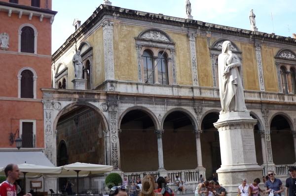Верона.Площадь Синьории.За памятником Данте видны арочное строение.Это  лоджия  дель  Консильо,дворец 15 века,наи карнизе дворца 5 водруженных  статуи(фото выше отчетливо видны все статуи) видных  людей  Вероны древнеримской  эпохи.Это Катулл, Плиний ...