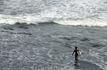 Сёрфер на пляже с чёрным вулканическим песком