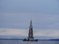 Затопленная колокольня на фоне облаков. Снято с борта катера.