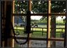 """Сквозь классические голландские окна """"на девять стекол"""" с перегородками, делящими окно на квадратики, видна зелень сада и лошадки."""