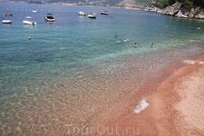 пляж рядом со Св. Стефаном. лето 2009 мелкая-мелкая галька, почти песок, около камней много морских ежей
