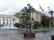 Пройдя через небольшой переулок мы вышли на La Plaza Puerta del Mar. Площадь довольно большая. Если стоять спиной к скульптуре, то слева будет городской ...