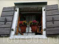 окна со ставнями и цветочные горшки