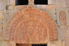 На барельефе изображена Дева Мария с младенцем на коленях, выполненная на богато орнаментированном фоне с большими буквами, переплетенными с орнаментами ...