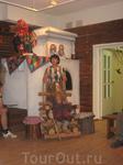 В доме кукол (Петрозаводск). Наш экскурсовод по дому кукол с куклой карельского водяного или лешего  (вроде бы?). На печке сидит домовой(?), не исключен ...