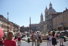 Рим. Piazza  Navona. Справа церковь Santa Agnese in Agone. В центре площади  Навона  фонтан 4-х рек(Fontana  dei Fiuti). Титаны  расположены по  четырем сторонам  основания фонтана,они символизируют