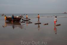 рыбаки вытаскивают лодку на сушу