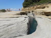 Узенький канал между невысокими песчаными скалами.