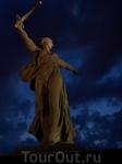 Вид ночью.Монумент освещается мощным прожектором.Величественно смотрится на фоне темно-синего неба.