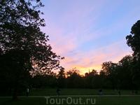 По берегу озера по дорожкам неспешно прогуливается публика, а небо начинает разыгрывать свой вечерний цвето-световой спектакль.