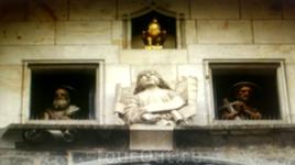 Два окошка, в которых появляются апостолы. Сверху в окошке петух.