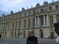 На фоне одного из зданий Большого Версальского дворца.