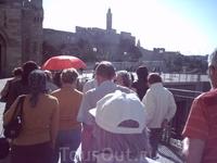 Впереди наш ориентир-красный зонт нашего экскурсовода. Вдали возвышается башня Давида