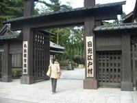 Вход в деревню. Вечером ворота закрываются, для спешаших на выход посетителей двое деревенских мужчин снова их распахивают, выкрикивая при этом что-то ...